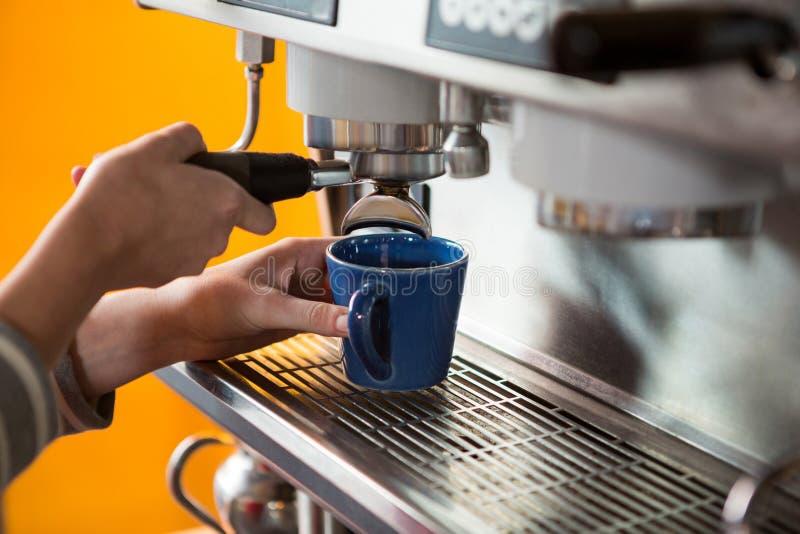 Vrouwelijke barista die koffie met machine in cafetaria voorbereiden stock foto's