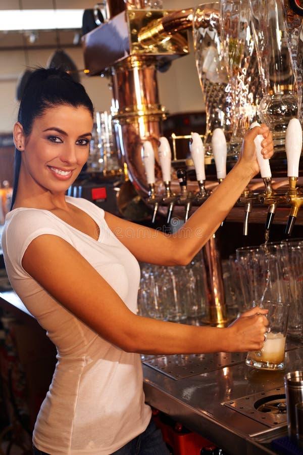Vrouwelijke barman die bier van het vat in bar onttrekken royalty-vrije stock foto's