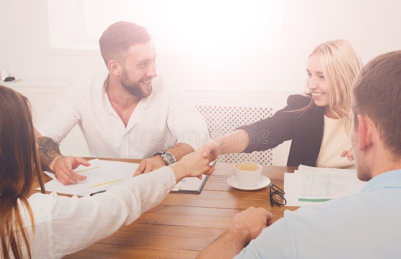 Vrouwelijke bedrijfshanddruk bij bureauvergadering, contractconclusie en su stock afbeelding