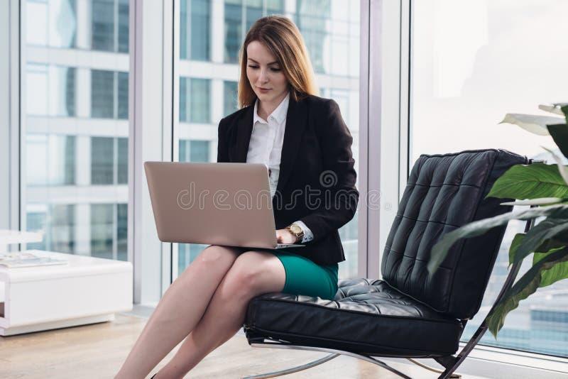 Vrouwelijke belangrijkste econoom die gegevens die laptop zitting gebruiken over leunstoel in modern bureau analyseren stock foto