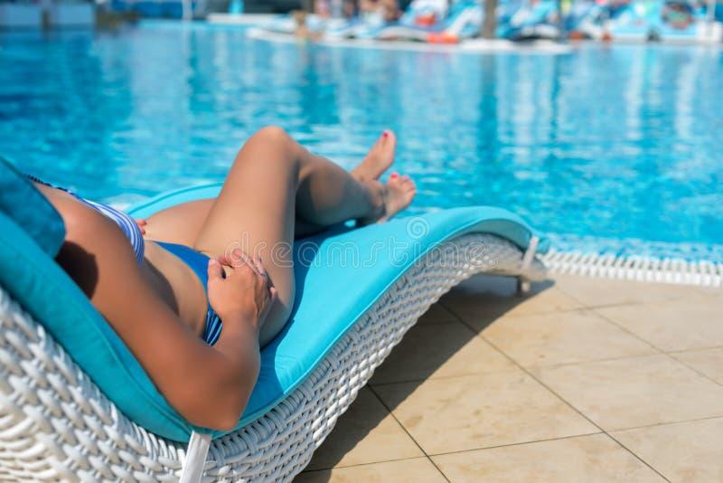 Vrouwelijke benen bij blauw water stock afbeelding