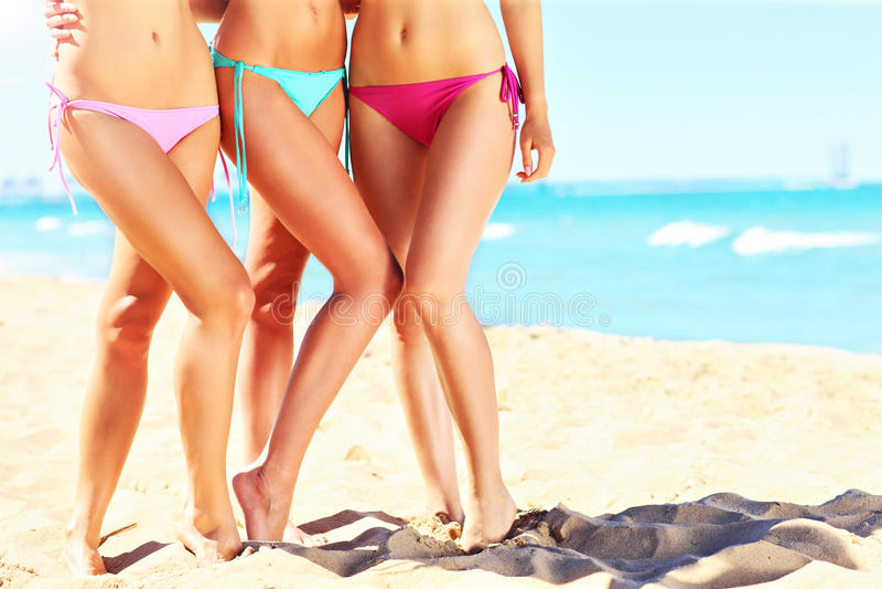 Vrouwelijke benen in bikini op het strand stock afbeelding