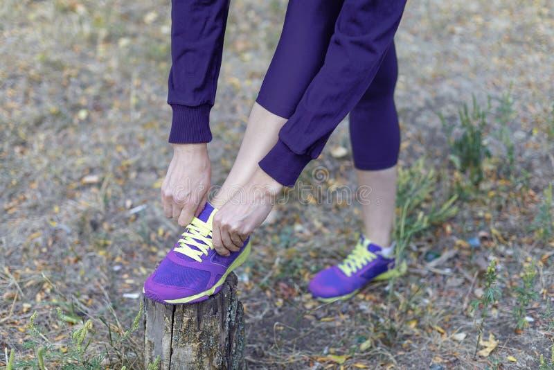 Vrouwelijke benen De vrouw in donkere violette sportkleding bindt heldere lilac tennisschoenen met kalkschoenveters, voorbereidin royalty-vrije stock foto's