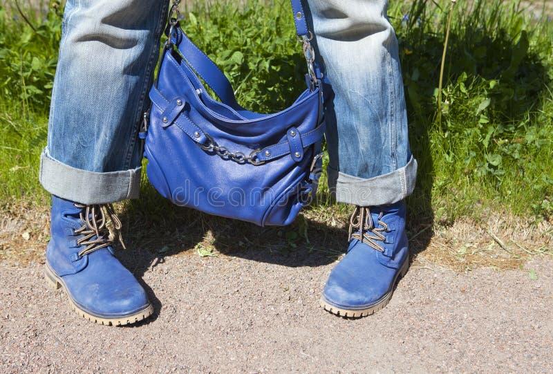 Vrouwelijke benen in jeans en laarzen met een blauwe zak op een de zomerachtergrond van een groen gras royalty-vrije stock foto