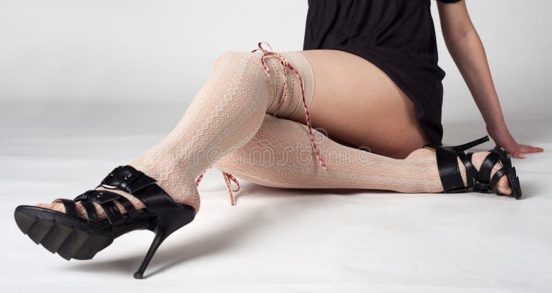 Vrouwelijke benen in lichte kousen en zwarte schoenen stock afbeeldingen