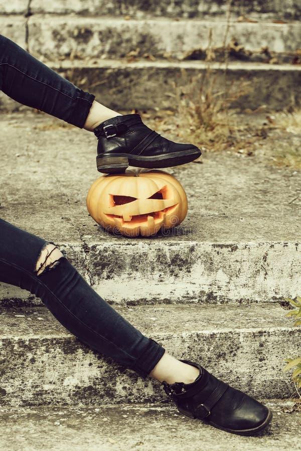 Vrouwelijke benen met Halloween-pompoen stock foto