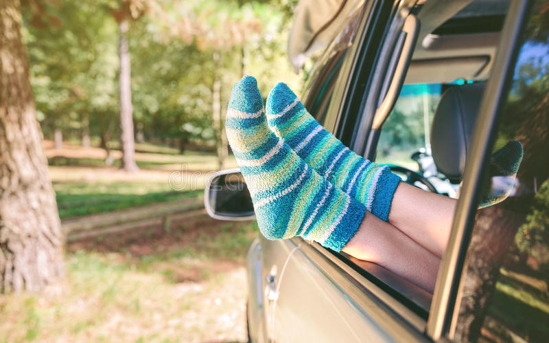 Vrouwelijke benen met sokken die over open venster rusten royalty-vrije stock afbeeldingen