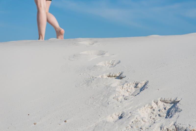 Vrouwelijke benen op horizon met tekens op zand royalty-vrije stock foto