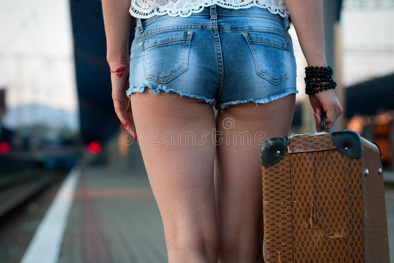 Vrouwelijke benen, in sexy borrels in schoenen met een oude koffer op royalty-vrije stock afbeelding
