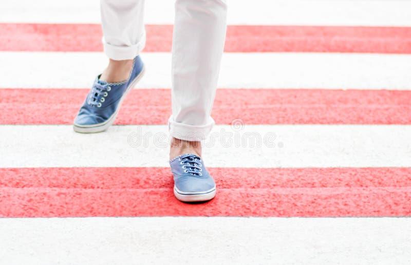 Vrouwelijke benen of voeten die rood zebrapad kruisen bij de zomerdag De vrouw kleedde zich in witte jeans en blauwe leeglopers d stock foto