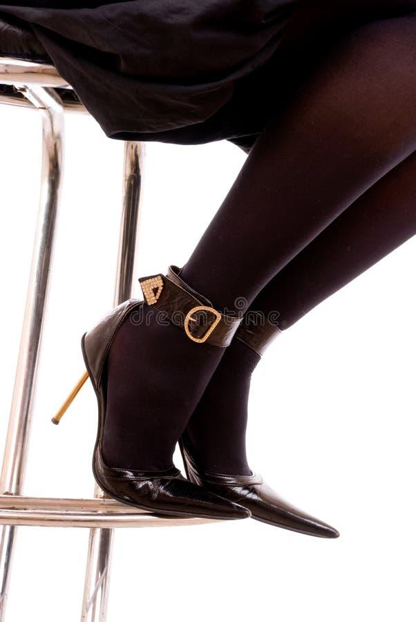 Vrouwelijke benen in zwarte kousen en schoenen op een hiel royalty-vrije stock afbeelding