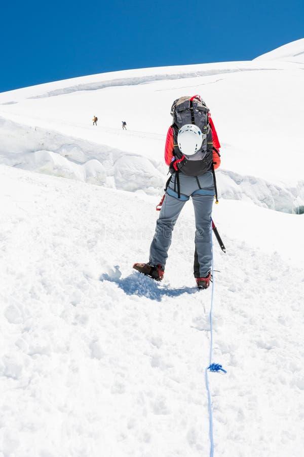 Vrouwelijke bergbeklimmer die een gletsjer stijgt royalty-vrije stock fotografie