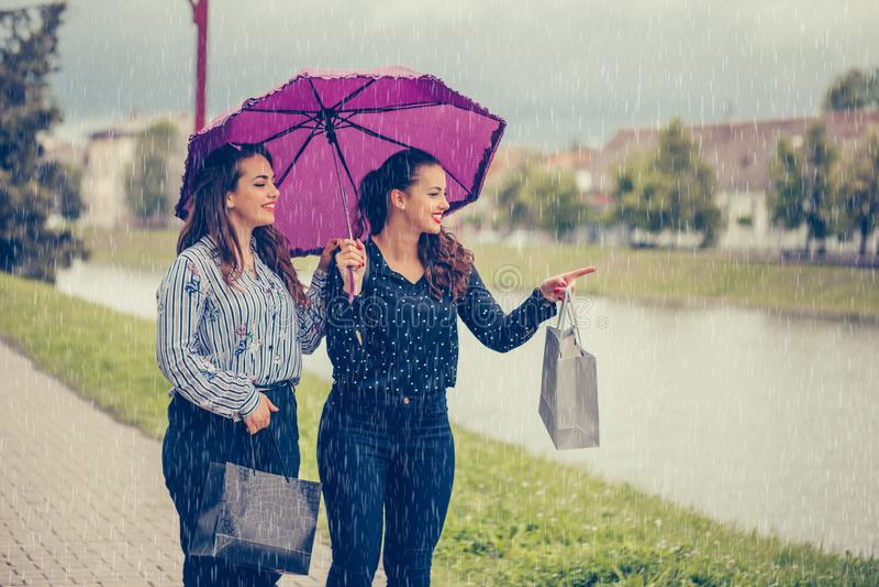 Vrouwelijke beste vriend twee die door de rivier met paraplu boven hoofd lopen royalty-vrije stock afbeelding