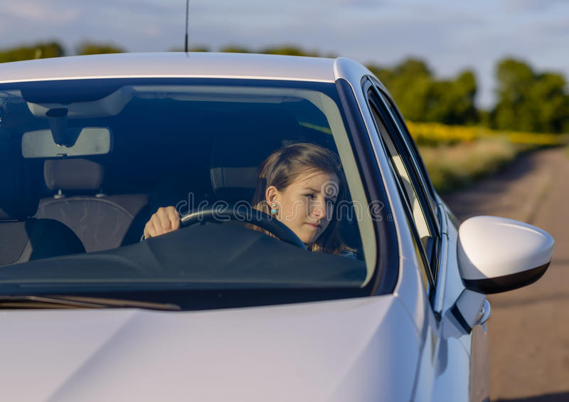 Vrouwelijke bestuurder die haar zijspiegel controleert royalty-vrije stock afbeeldingen