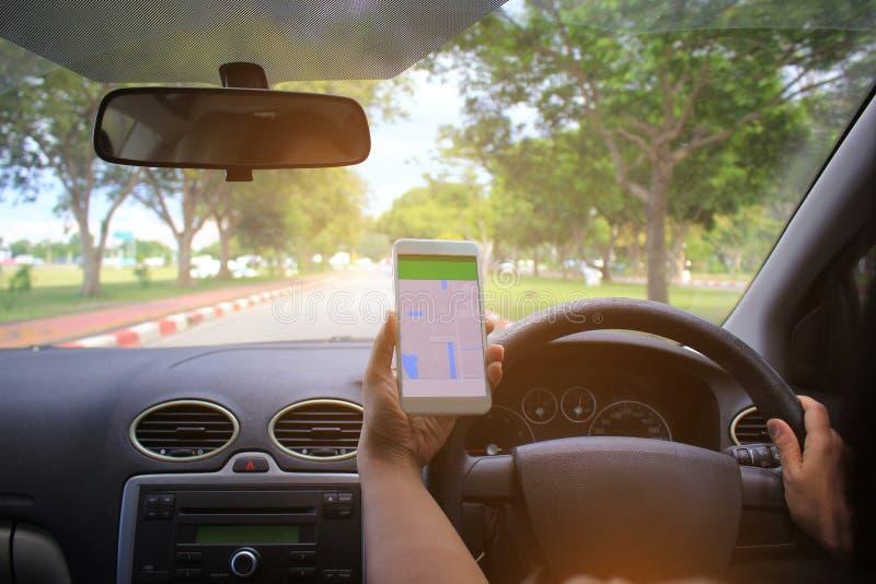 Vrouwelijke bestuurdershanden die het paneel van de autoleiding met kaartgps navigatietoepassing houden op de weg stock afbeeldingen
