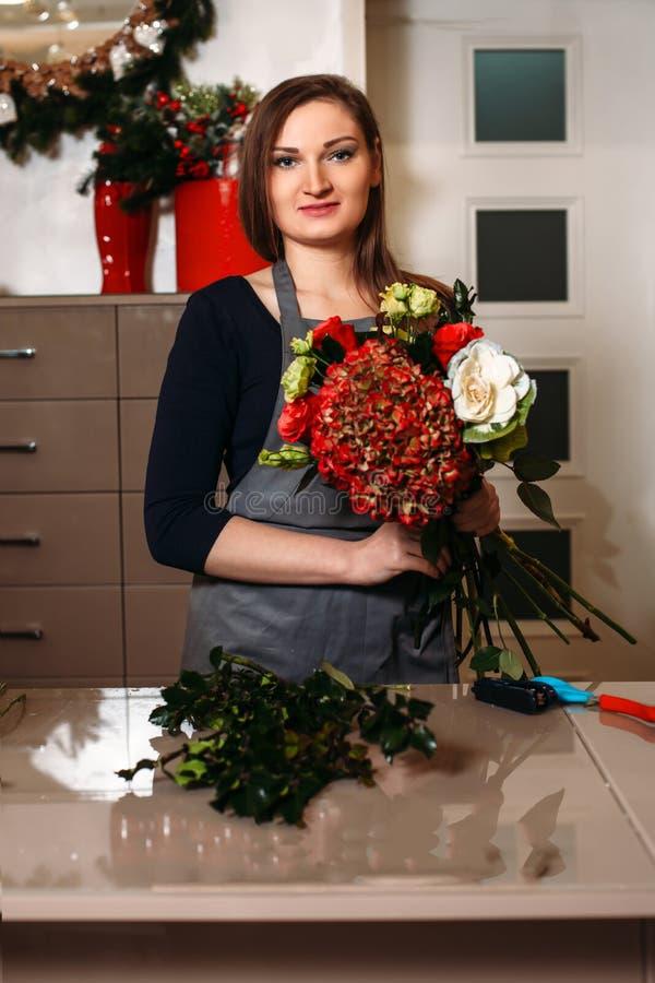 Vrouwelijke bloemist die met bloemen werken stock foto