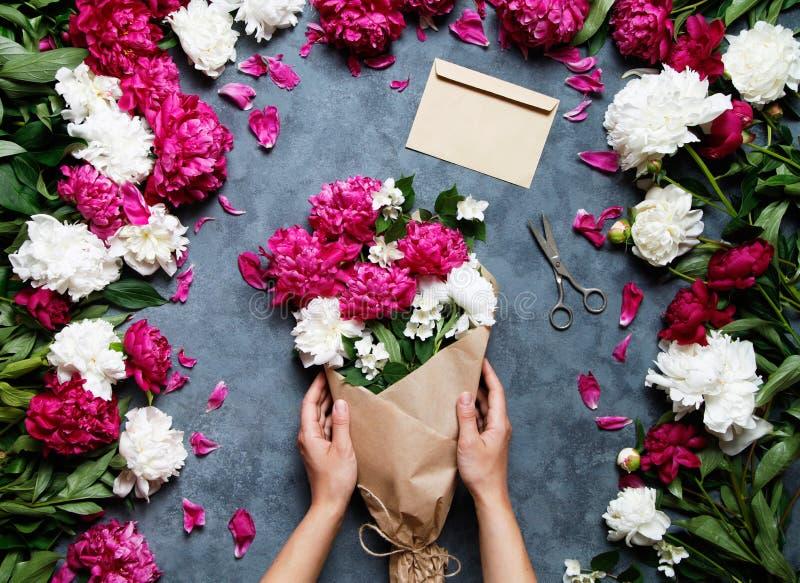Vrouwelijke bloemist die mooi boeket houden bij bloemwinkel Bloemist op het werk: mooie vrouw die de zomerboeket van pioenen make stock fotografie