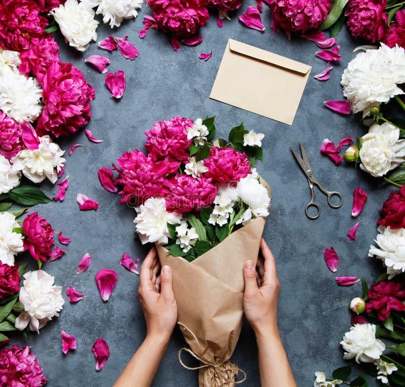 Vrouwelijke bloemist die mooi boeket houden bij bloemwinkel Bloemist op het werk: mooie vrouw die de zomerboeket van pioenen make royalty-vrije stock fotografie