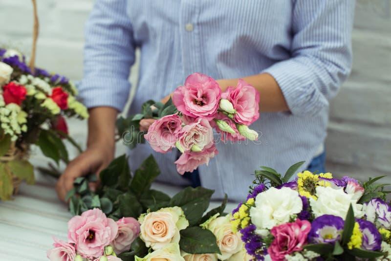 Vrouwelijke bloemist die mooi boeket maken bij bloemwinkel royalty-vrije stock afbeelding