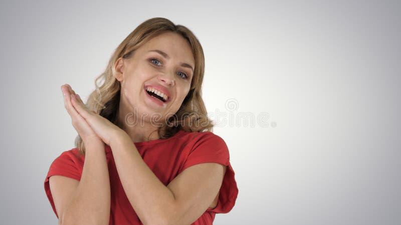 Vrouwelijke blondevrouw die aan camera spreken die zeer gelukkig op gradiëntachtergrond zijn stock fotografie