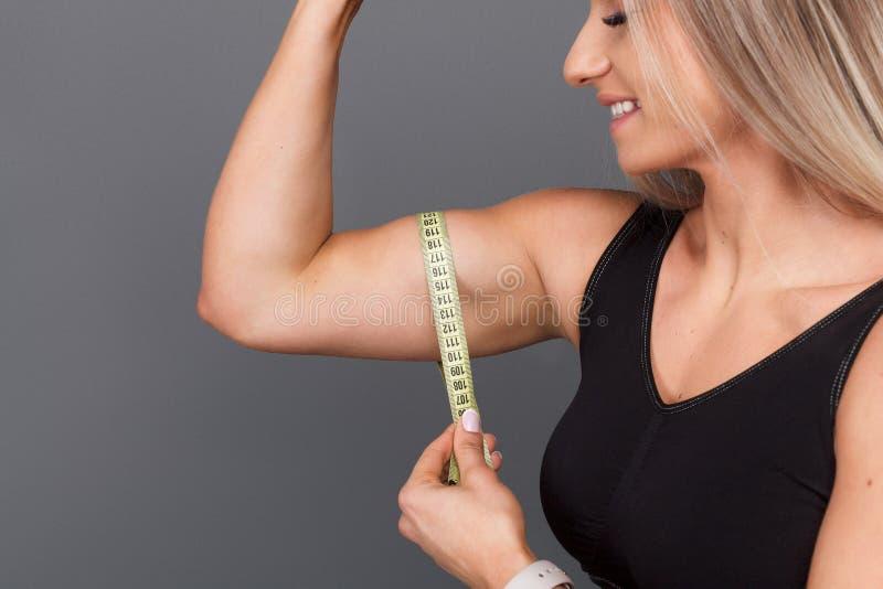 Vrouwelijke bodybuilder die bicepsen meten stock afbeelding