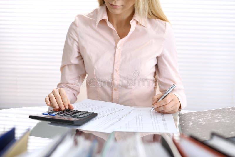 Vrouwelijke boekhouder of financiële inspecteur die verslag uitbrengen, of saldo berekenen controleren De Fiscus Servic stock afbeelding