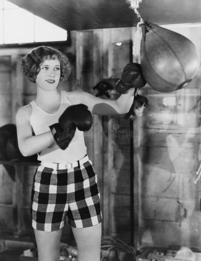 Vrouwelijke bokser die ponsenzak met behulp van (Alle afgeschilderde personen leven niet langer en geen landgoed bestaat Leveranc royalty-vrije stock foto's