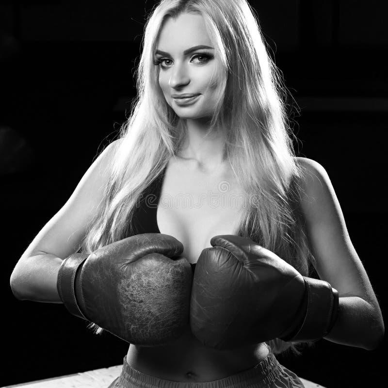 Vrouwelijke bokser die in rode bokshandschoenen op houten doos zitten stock afbeeldingen