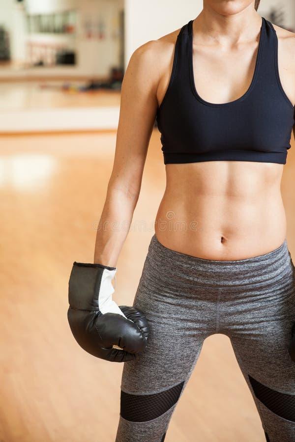 Vrouwelijke bokser met gestemde abs in een gymnastiek stock fotografie