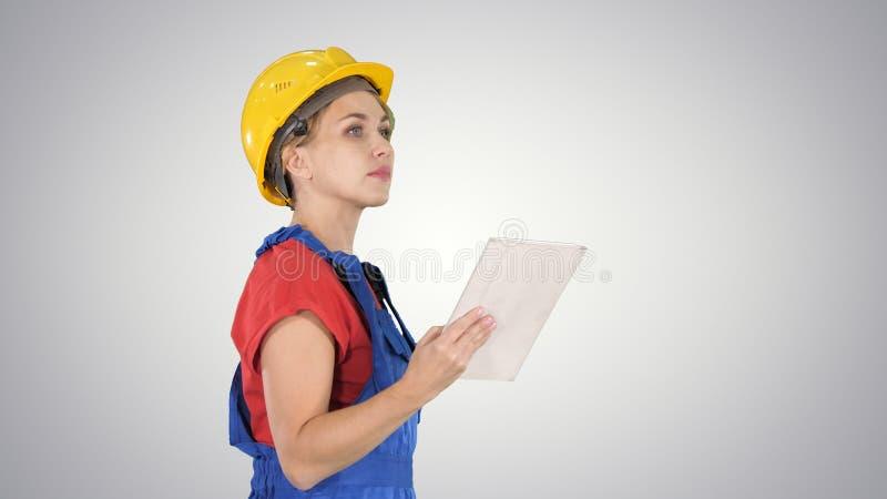 Vrouwelijke bouwingenieur die tablet bekijkt en voorwerp controleert op gradiëntachtergrond stock foto
