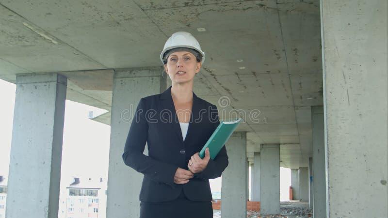 Vrouwelijke bouwmanager die met blauwdruk op bouwterrein het project voorleggen die camera bekijken stock afbeelding