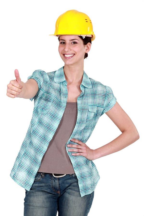 Vrouwelijke bouwvakker duim-omhoog stock afbeeldingen