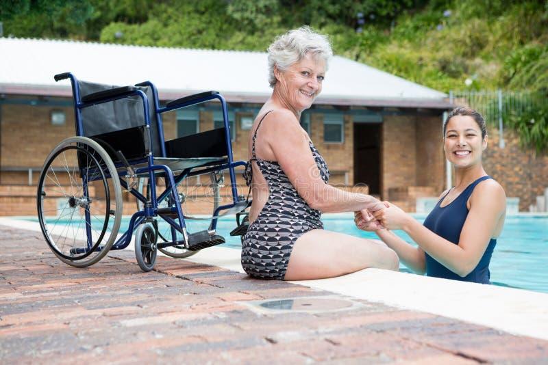 Vrouwelijke bus en hogere vrouw die bij poolside glimlachen royalty-vrije stock foto's