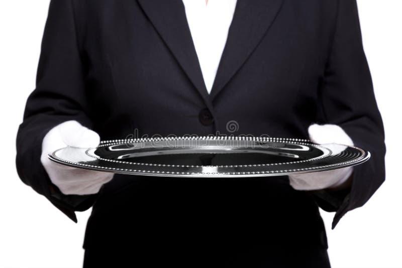 Vrouwelijke butler die een zilveren dienblad geïsoleerds houdt