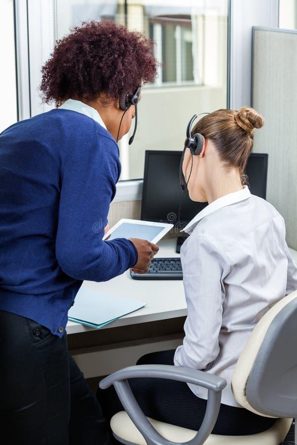Vrouwelijke Call centreagenten die Tabletcomputer met behulp van stock foto's