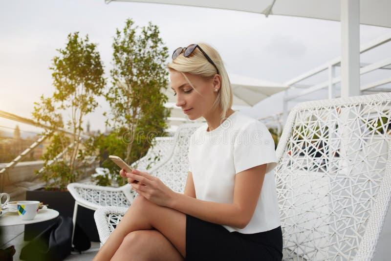 Vrouwelijke CEO zoekt informatie in Internet via celtelefoon, terwijl op hotelbalkon zit stock foto