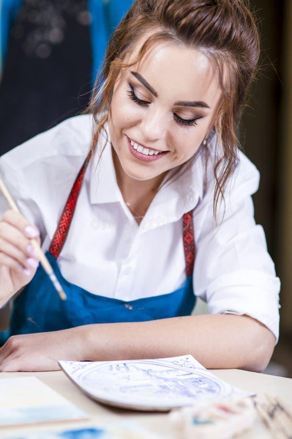 Vrouwelijke Ceramist in Eenvormige Verglazing en het Schilderen Ceramische Ambachten stock foto's