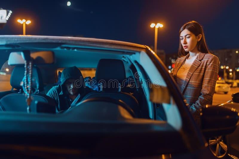 Vrouwelijke chauffeur in de auto, inbreker op de achterbank royalty-vrije stock afbeelding