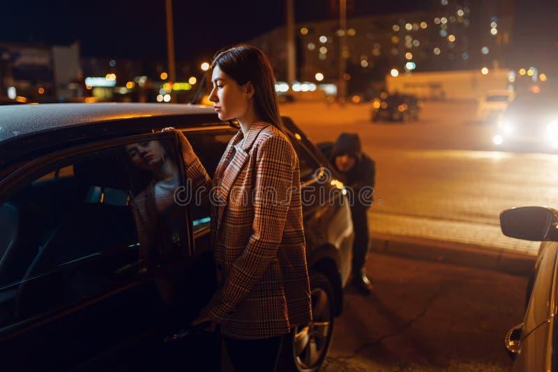 Vrouwelijke chauffeur in de auto, rover die achterop glipt stock fotografie