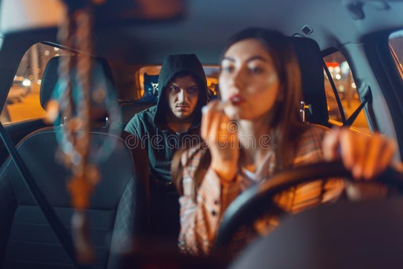 Vrouwelijke chauffeur en vastzittende autoinbreker op de achterbank stock fotografie