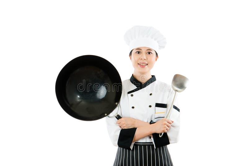 Vrouwelijke chef-kok die wok en spatelhulpmiddelen tonen stock foto's