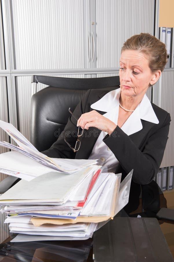 Vrouwelijke chef-kok in het bureau met heel wat documenten royalty-vrije stock fotografie