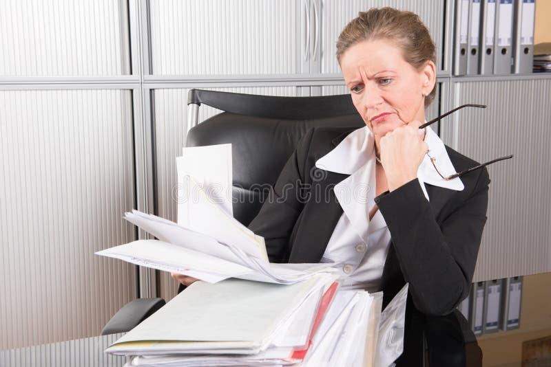 Vrouwelijke chef-kok in het bureau met teveel werk stock fotografie