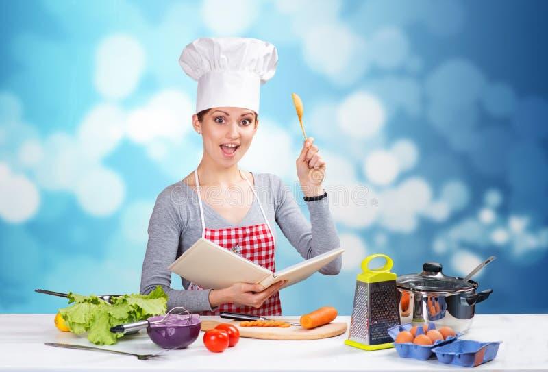 Vrouwelijke chef-kok met het kookboek en een houten lepel op blauwe achtergrond stock foto