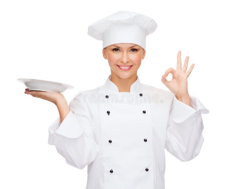 Vrouwelijke chef-kok met lege plaat die o.k. teken tonen stock foto
