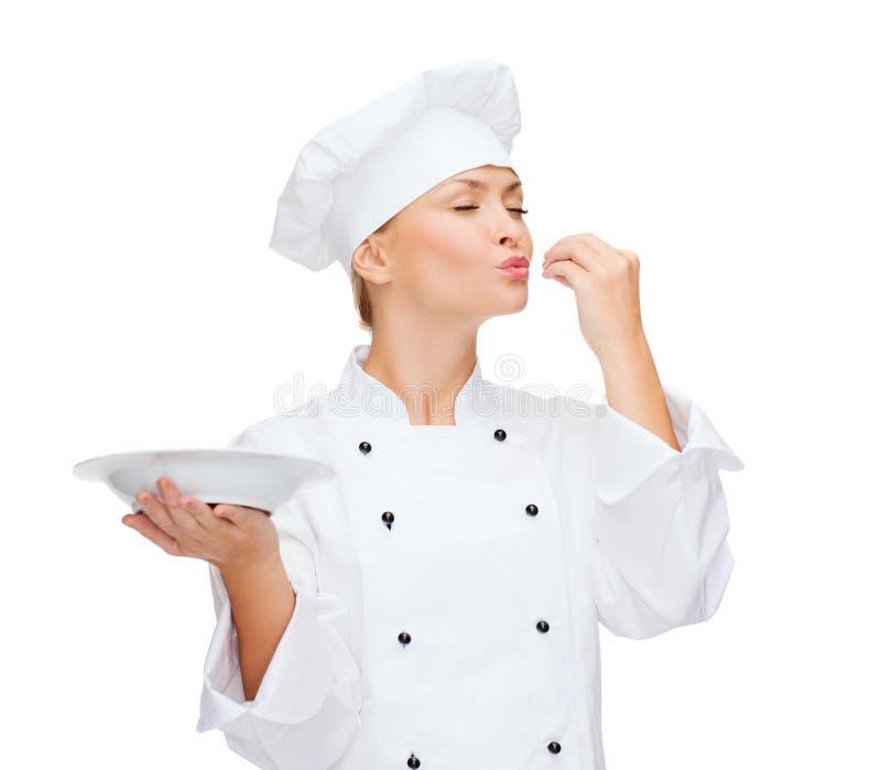 Vrouwelijke chef-kok met plaat die heerlijk teken tonen stock foto