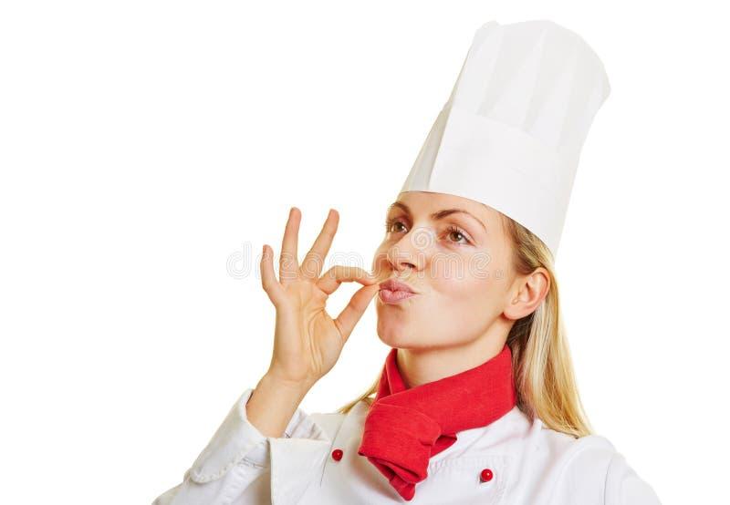 Vrouwelijke chef-kokkok die teken van beste smaak met hand geven royalty-vrije stock fotografie