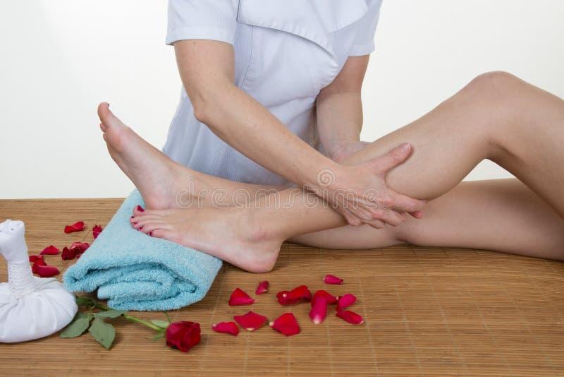 Vrouwelijke chiropracticus die patiëntenbeen controleren op massagelijst royalty-vrije stock foto's