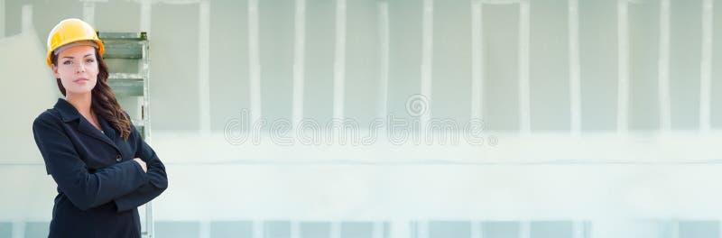 Vrouwelijke Contractant die Bouwvakker dragen tegen Drywall Bannerachtergrond met Ladder royalty-vrije stock fotografie