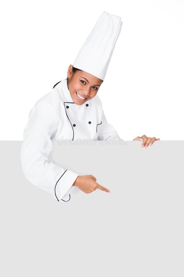 Vrouwelijke Cook die zich achter het Aanplakbiljet bevinden stock afbeelding
